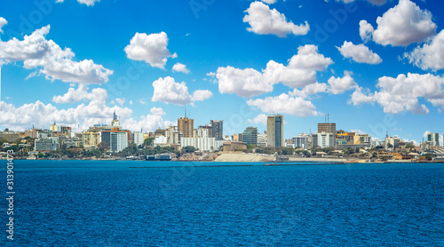 View of the Senegal capital of Dakar, Africa. It is a city panorama taken from a boat. There are large modern buildings and a blue sky with clouds. #313901473