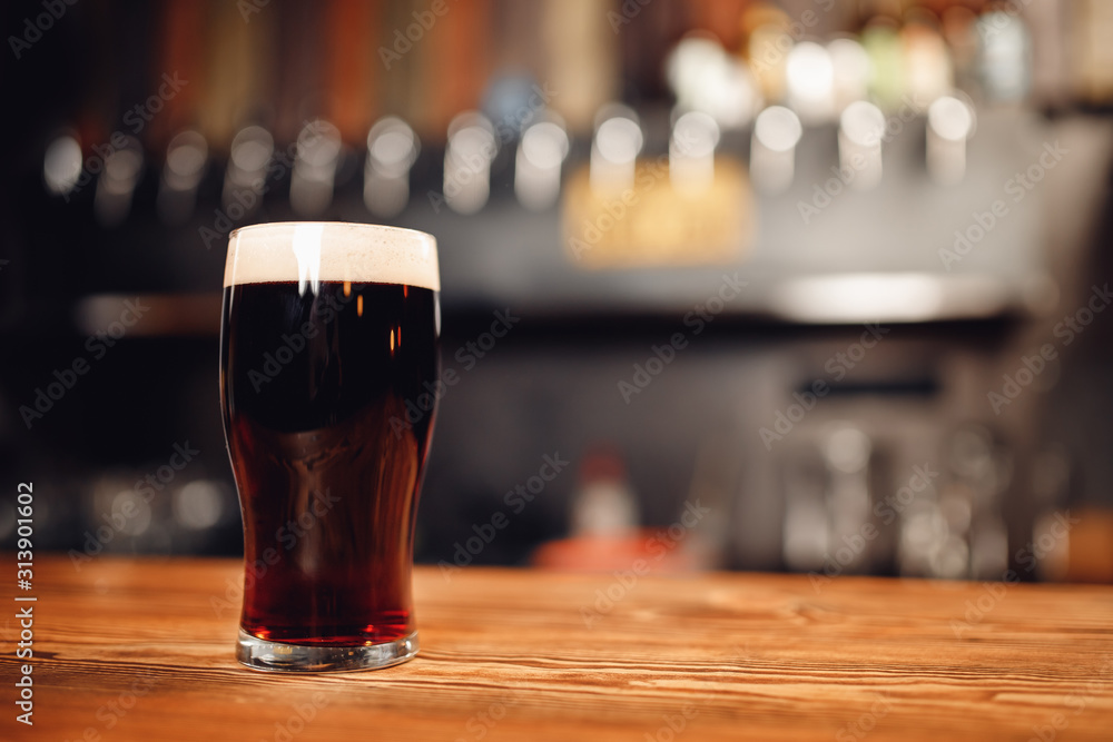 Fototapeta Glass with cold unfiltered beer on background of bar