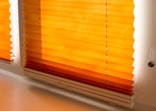 Pleated Blinds With Orange Folded Fabric On The Window Close Up. Cordless Bottom Up Top Down Pleated Shade With White Lower Bar.