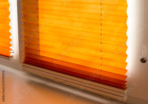 Pleated blinds with orange folded fabric on the window close up Canvas-taulu