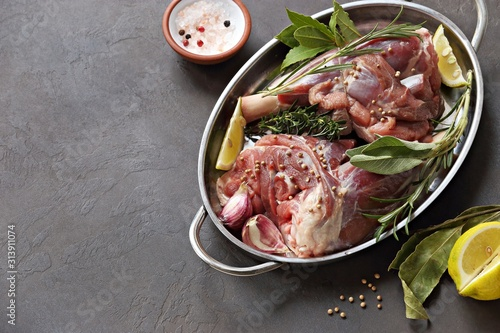 Fototapeta Raw lamb shanks with herbs and spices. Flat layot on dark concrete background. Copy space obraz
