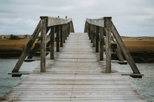 Low Angle View Of Boardwalk Bridge Over Sea Inlet And Salt Marsh