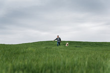 Teenage Boy Running Across A Grassy Field With His Dog On Cloudy Day.