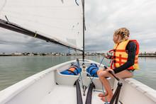 Tween Girl Sailing In A Small Sailboat