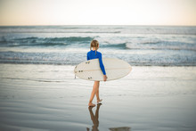 Girl Walking On Beach With Surfboard During Sunset