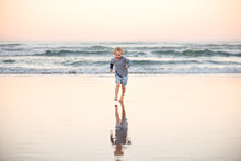 Happy Little Boy Running On Beach