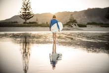 Tween Girl On New Zealand Beach Holding Surfboard