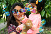 Sisters Playing And Making Fun With Soap Bubbles At Outdoors