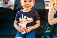 Young Boy Smiling Eating Snow Cone With Dad And Sister