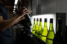 Man Placing Bottles On Conveyor