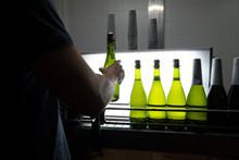 Worker Shaking Bottle At Produ...