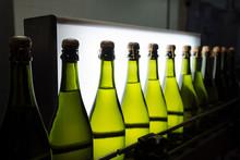 Green Lighted Bottles On Industrial Conveyor