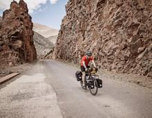 A Cyclist Rides Through A Rock Cut On A Mountain Road In Morocco