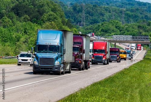 Fototapeta Blue Semi climbs Interstate Hill In Heavy Traffic obraz