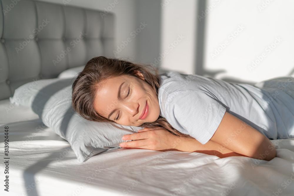 Fototapeta Bed Asian girl happy smiling sleeping on stomach sleeper resting head on foam pillow. Healthy sleep.