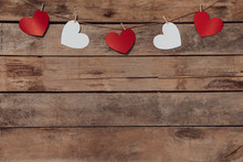 Old Wooden Background With A Garland Of Red And White Hearts. Natural Rope And Clothespins. Concept Of Recognition Of Love, Romantic Relationships, Valentine's Day In Grunge Style. Copy Space