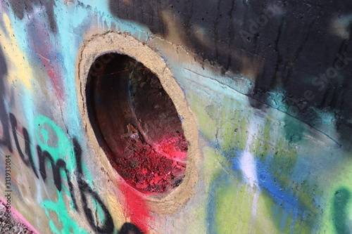 A large pipe opening in a wall covered in graffiti