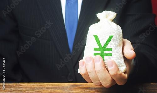 Man holds out a Yen yuan money bag Fototapet