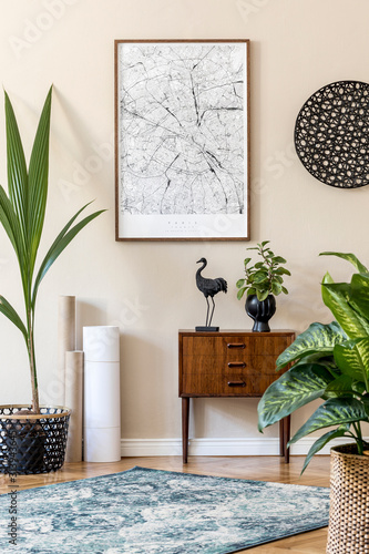Modern scandinavian living room interior with brown mock up poster frame, design retro commode, rattan decor, carpet, plants, maps and elegant accessories. Template. Stylish home staging. Japandi.