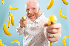 Bald Man Surrounded By Bananas