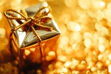 Golden Gift On Defocused Lights Background Close Up.