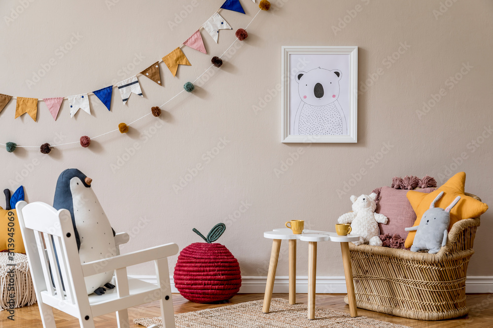 Fototapeta Stylish scandinavian interior of kid room with mock up poster frame, design furnitures, natural toys, hanging colorful flags, plush animal, child accessories and teddy bears. Modern home decor.