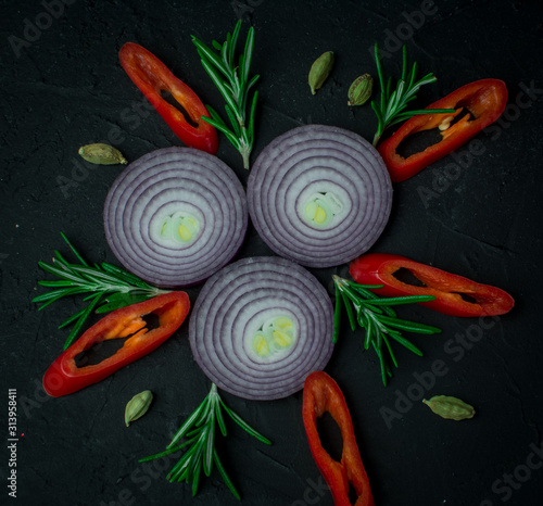 red hot chelli  peppers herbs red onion on black background