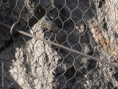 Fotografie, Obraz metal mesh  and wires protects  roads from landslide and rockfall