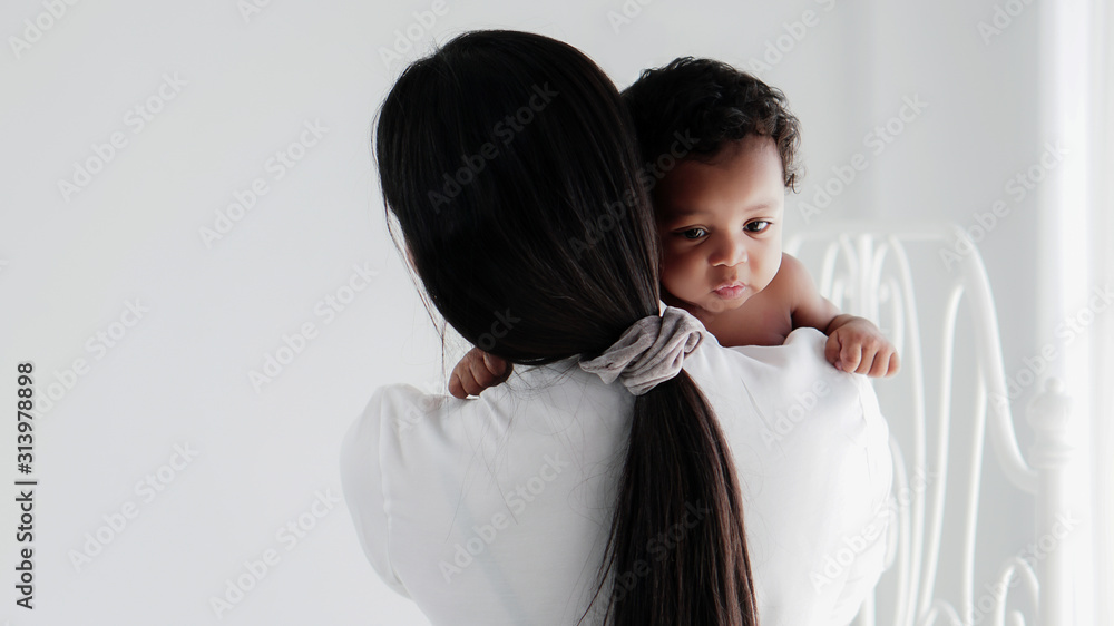 Fototapeta portrait of asian mother and her black mixed race baby girl in white room