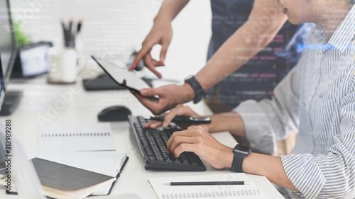 Fototapeta Side shot of young Programmer team while brainstorming/deciding on work at the work desk. obraz