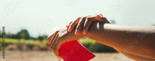 Photo close up young woman applying sunscreen lotion on hand