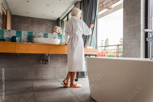 Elderly lady in bathrobe looking in the mirror Canvas Print