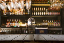 Empty Wooden Bar Counter With Defocused Background And Bottles Of Restaurant, Bar Or Cafeteria Background.