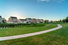 Grassy Pond And Pathway Winding Through Lush Green Lawn With Homes Background
