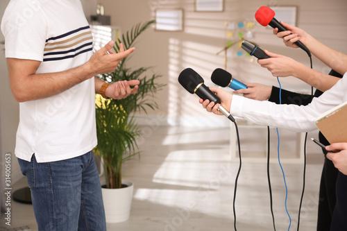 Group of journalists interviewing man in room, closeup Wallpaper Mural