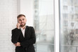 Young businessman talking on phone near window at home