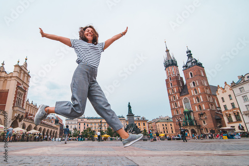 Fototapeta city tourism concept woman jumping at krakow market square saint mary church on background obraz