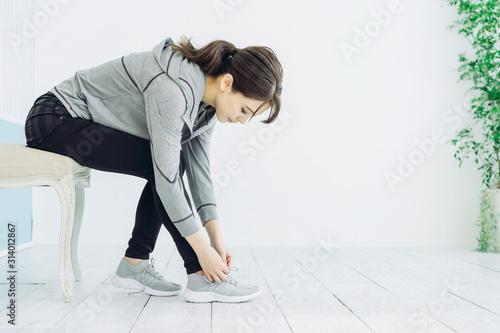 靴紐を結ぶ女性 Poster Mural XXL