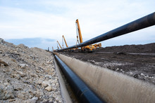 Gas Pipeline Construction. Heavy Duty Construction Machines Placing Gas Pipe Into The Ground.