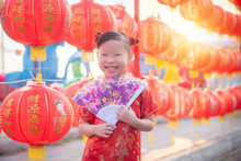 Little Asian Girl Wearing Chinese Treditional Costume Standing With Red Lantern And Smiling In Chinese New Year Festival.