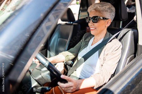 obraz PCV Smiling senior lady in sunglasses sitting in auto