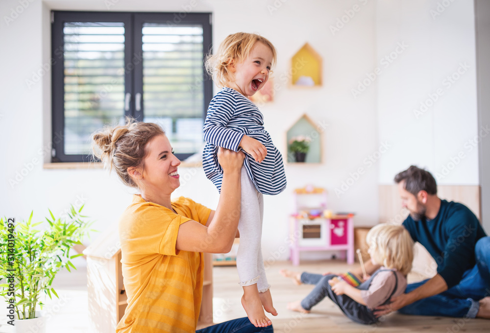 Fototapeta Young family with two small children indoors in bedroom having fun.
