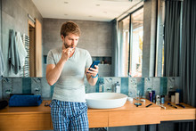 Handsome Man Brushing Teeth And Using Cellphone