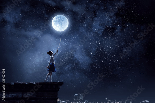 Fotografia Kid girl catching moon. Mixed media