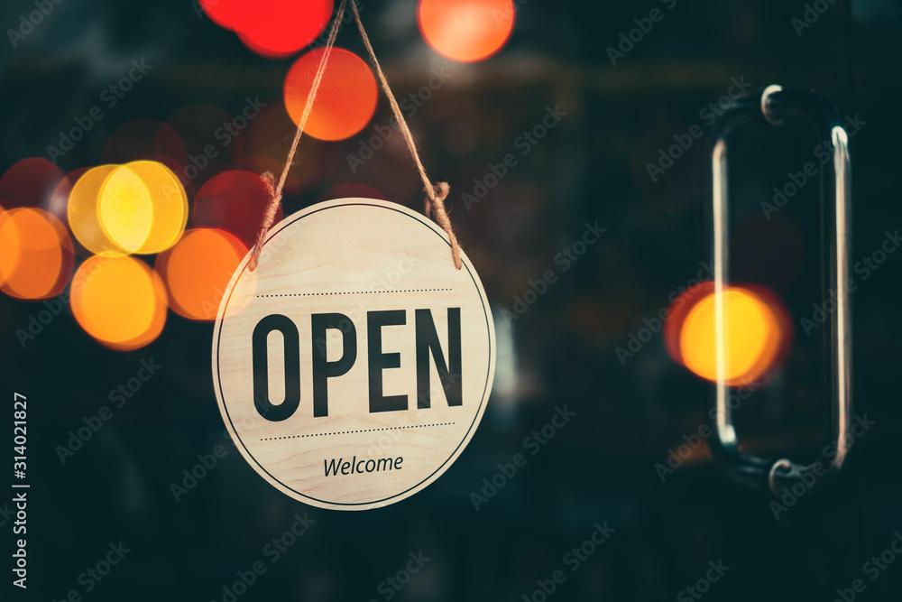 Fototapeta Open sign broad hanging on wood door front of cafe.