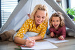 A cute small girl with mother indoors at home, drawing pictures.