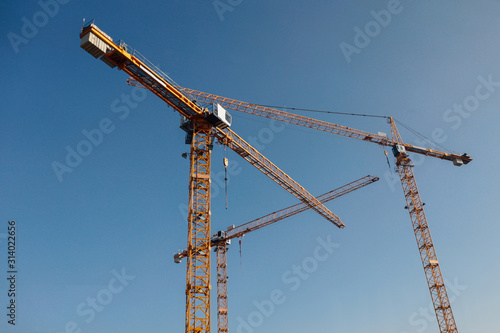 Luffing jib tower crane at large scale construction site over blue sky Fototapeta