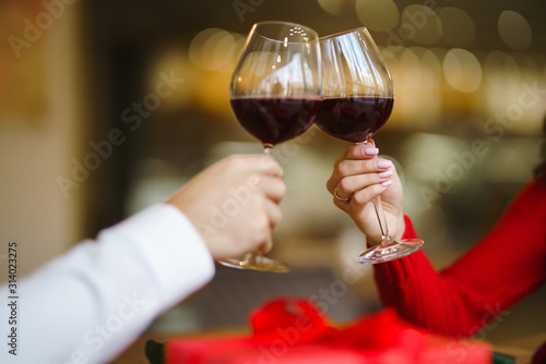 Hands holding glasses of wine on restaurant background. Couple clink glasses with red wine. Romance at restaurant for Valentine's Day- concept. Relationship & Birthday concept.