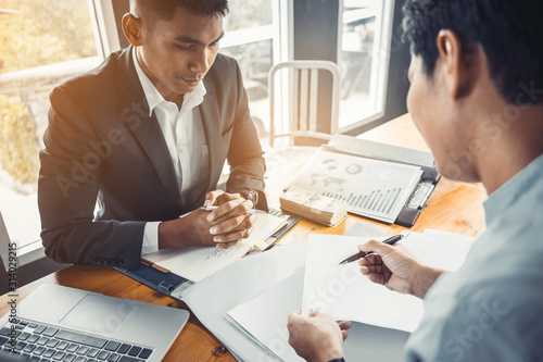 Loan business finance businessman explain business report from data analysis or bank marketing for loan money. Selected focus.