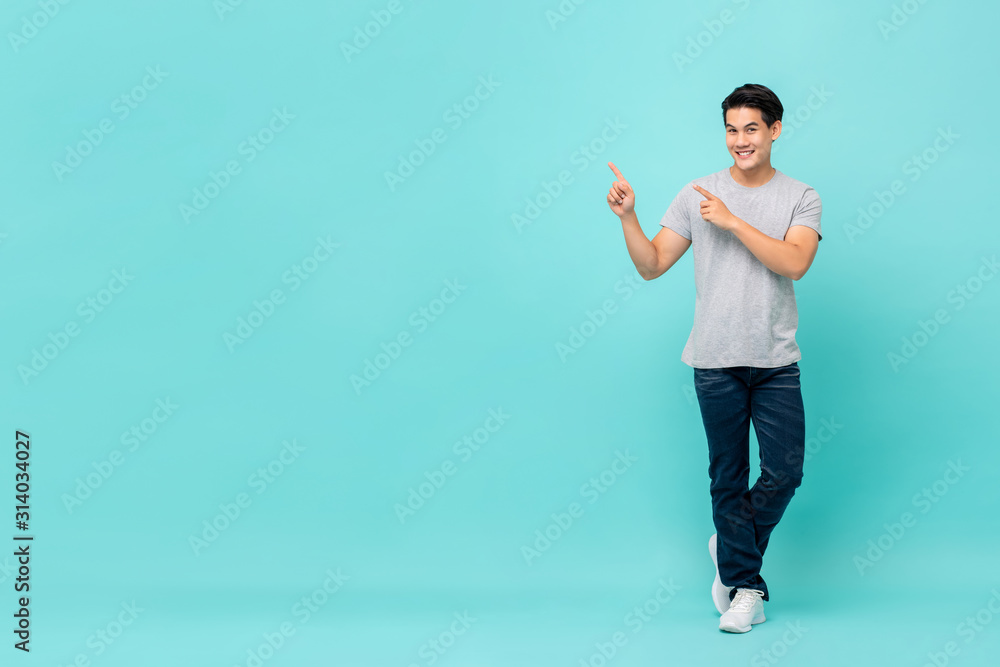Fototapeta Confident smiling young Asian man pointing hands to copy space aside